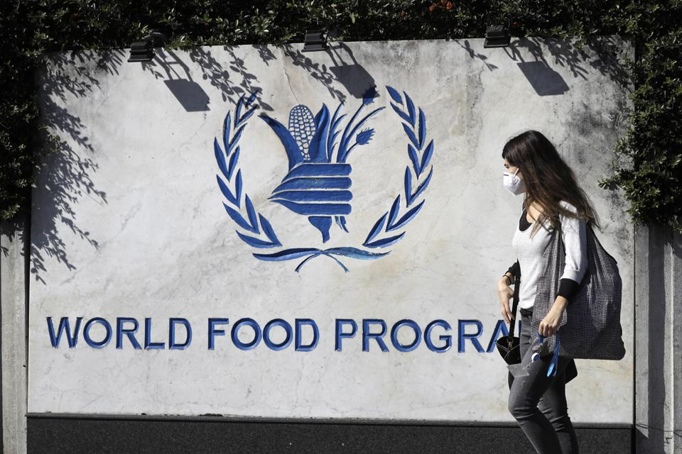 A woman walks past a sign at the entrance of the United Nations World Food Programme.