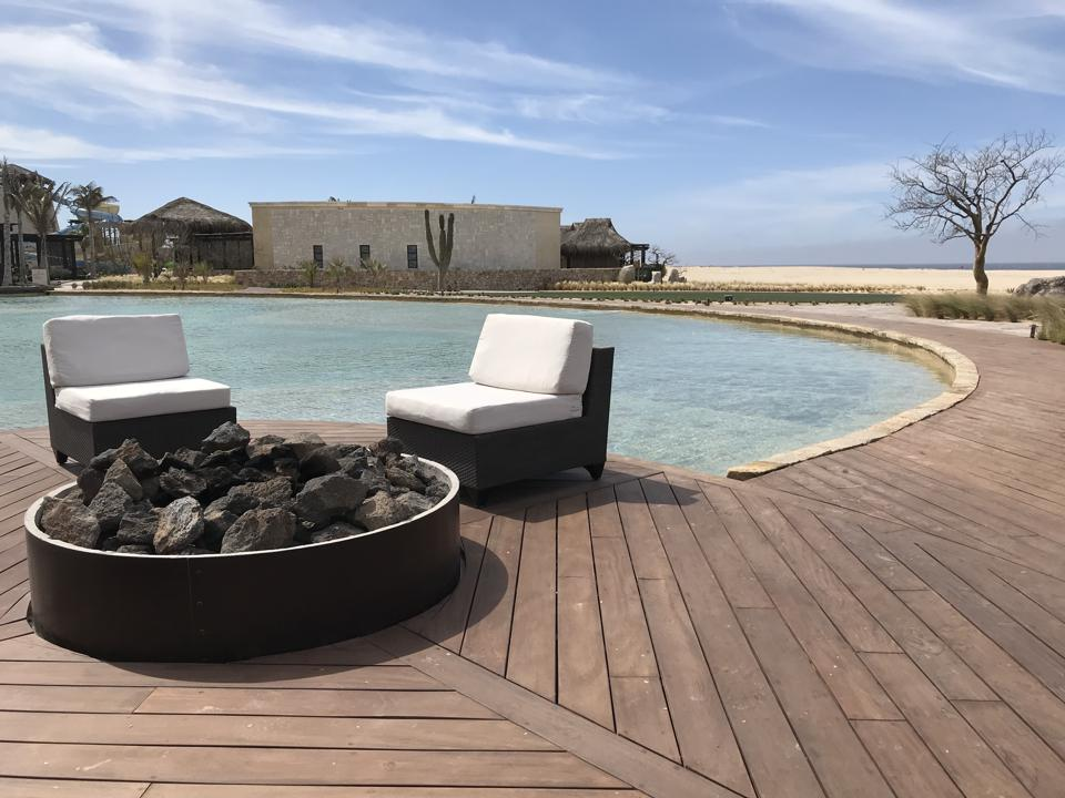 Two chairs next to a fire pit, in front of a pool; in the background is the spa and the beach.