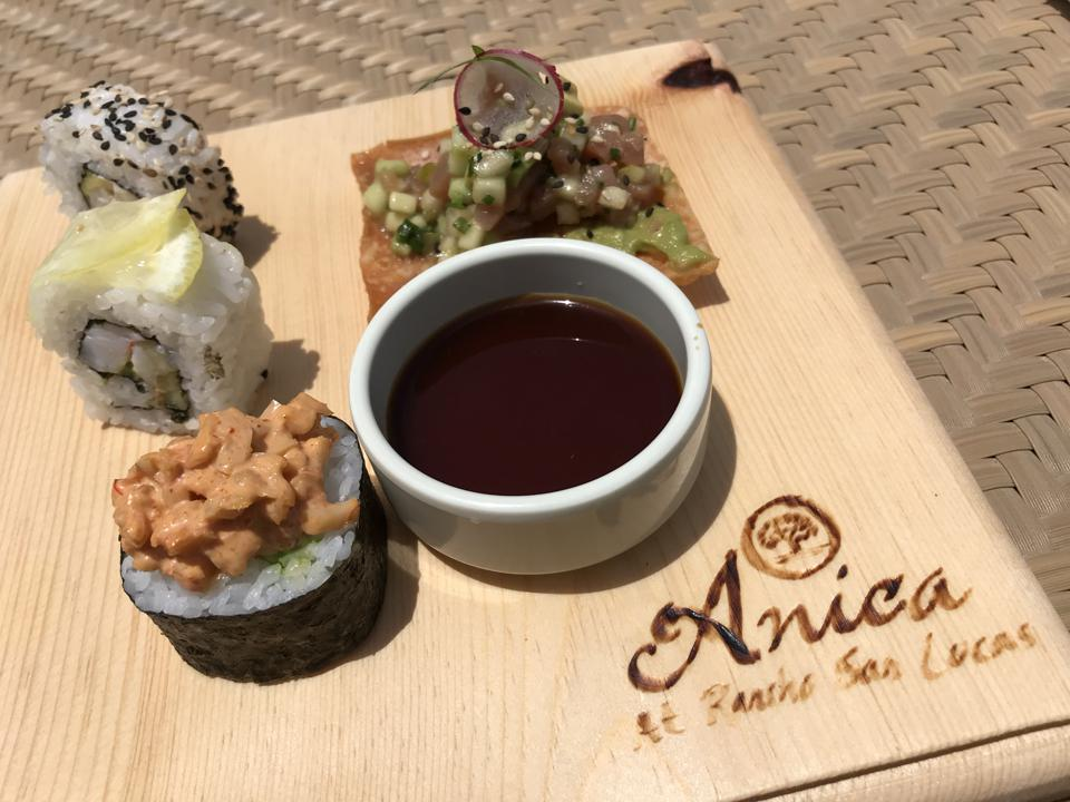 A wooden board with Anica's name burned into it, on top of which sits pieces of sushi, a ramekin of soya sauce, and a ceviche-topped square cracker