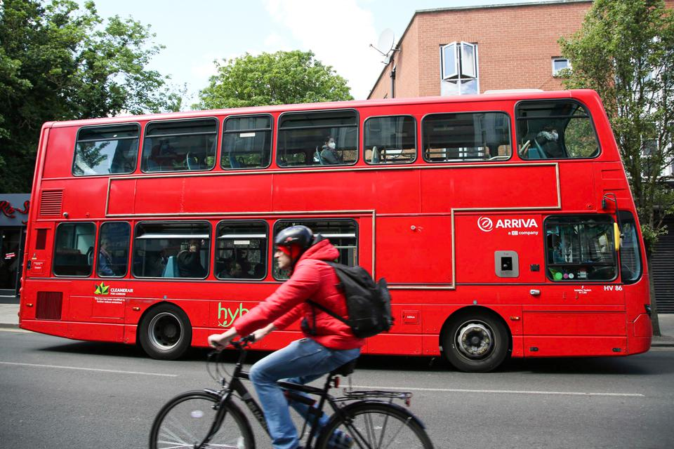 A cyclist rides next to a London bus with Passengers wearing...