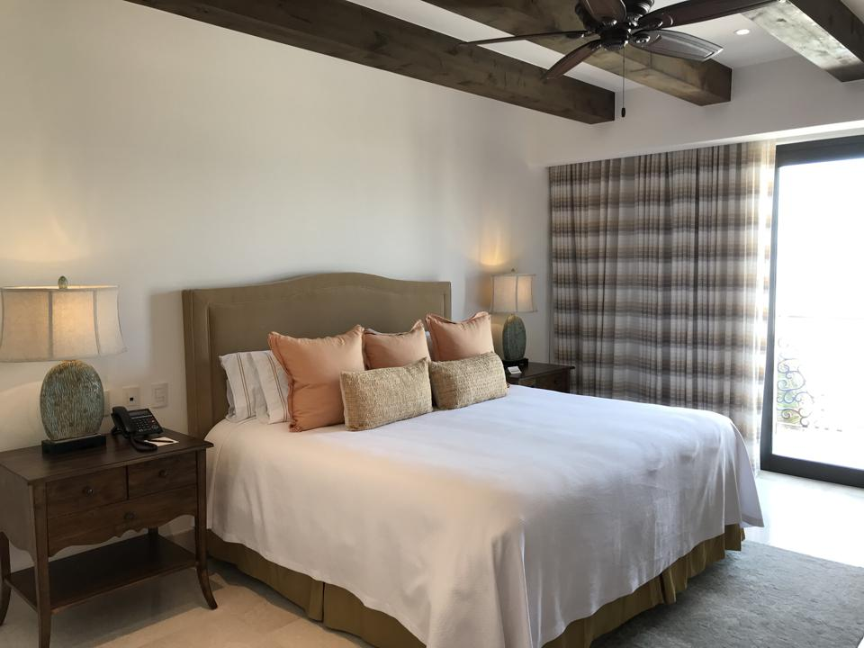 A king-sized bed with white cover and earth-toned throw pillows, with a bedside table, curtained doors go out to a balcony, and the ceiling has wooden beams and a fan