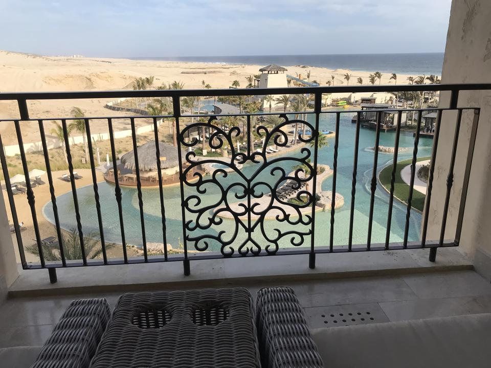 Through the iron railings of the balcony, the twisting blue of the lagoon pool with its palm tress and poolside restaurants, with empty sand dunes and the ocean in the background