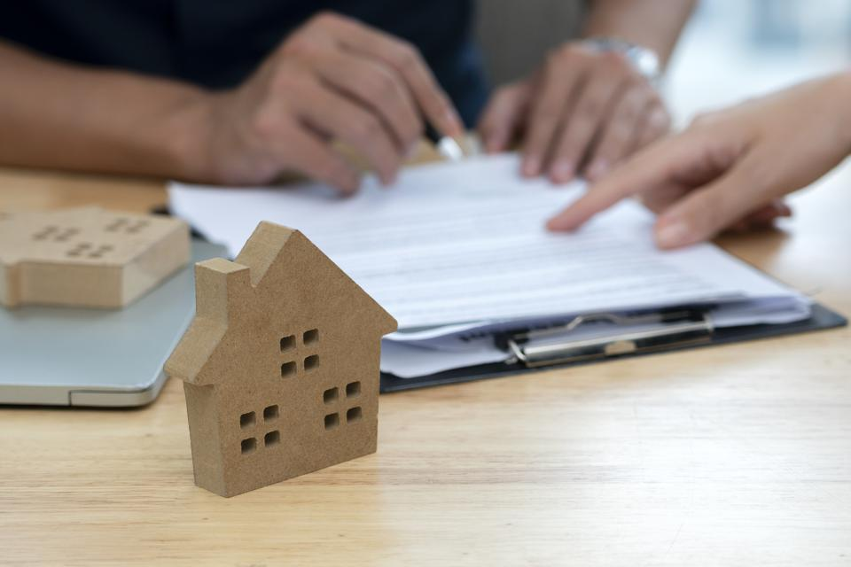 Customer signing a real estate contract in real estate agency.