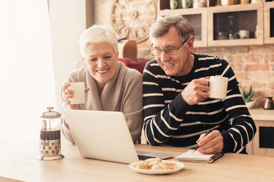 Cheerful senior couple looking at laptop in kitchen