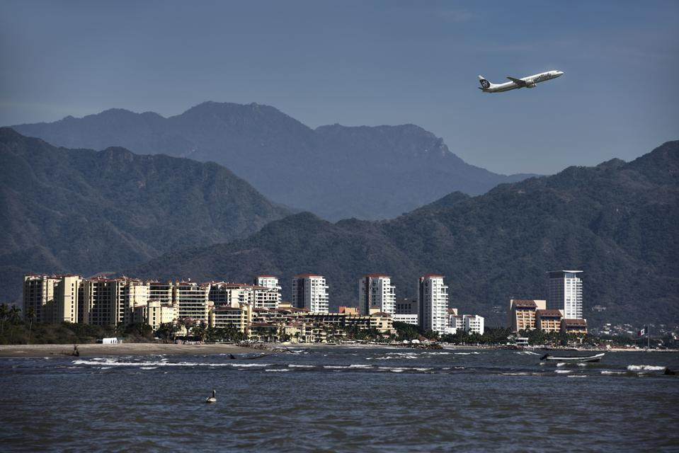 Jet plane taking off from Puerto Vallarta airport with Pacific ocean and mountains