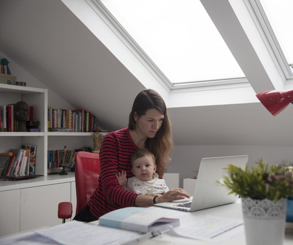 A Woman strives to work at home while holding her six-month-old daughter at a desk.