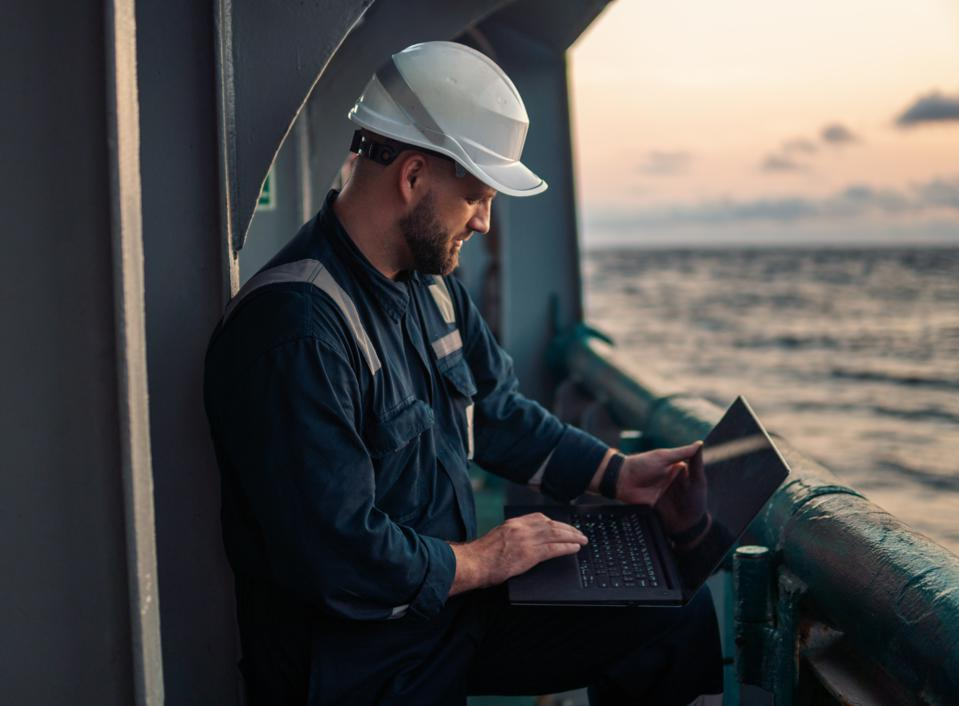Marine chief officer or captain on deck of vessel or ship watching laptop