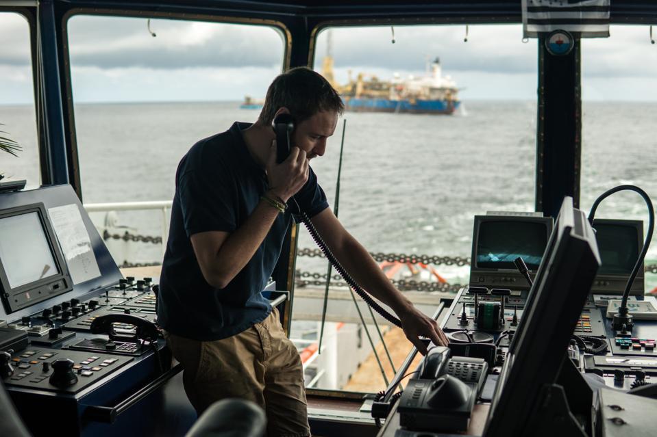 Deck navigation officer on the navigation bridge. He looks through binoculars