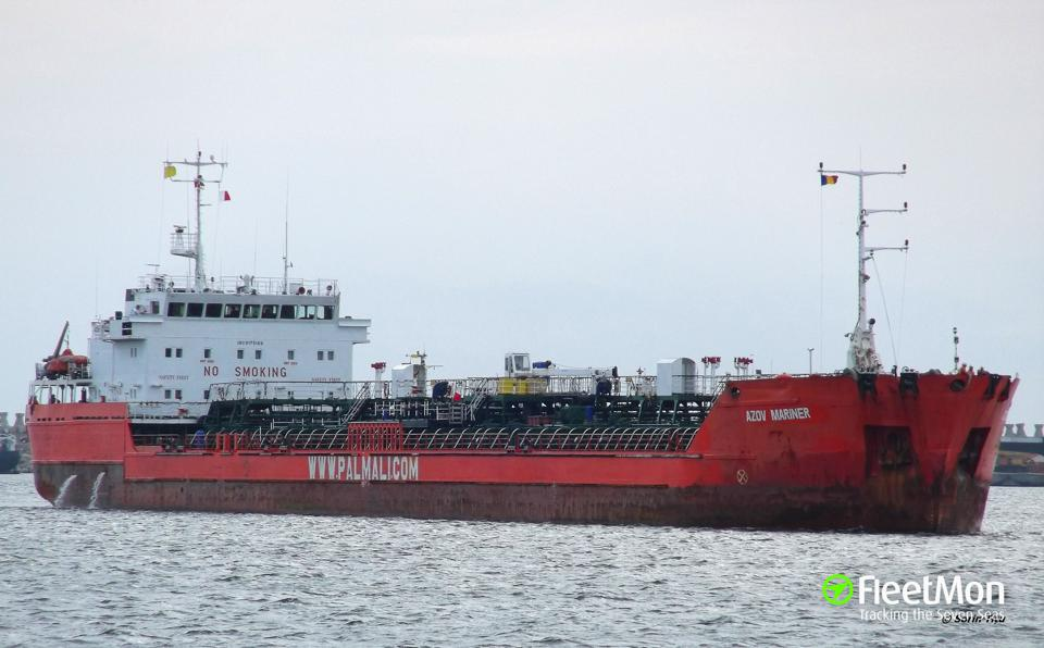 A mostly red oil tanker sailing in water.