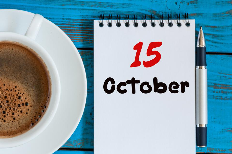 October 15th. Day 15 of month, hot coffee cup with calendar on accauntant workplace background. Autumn time. Empty space for text