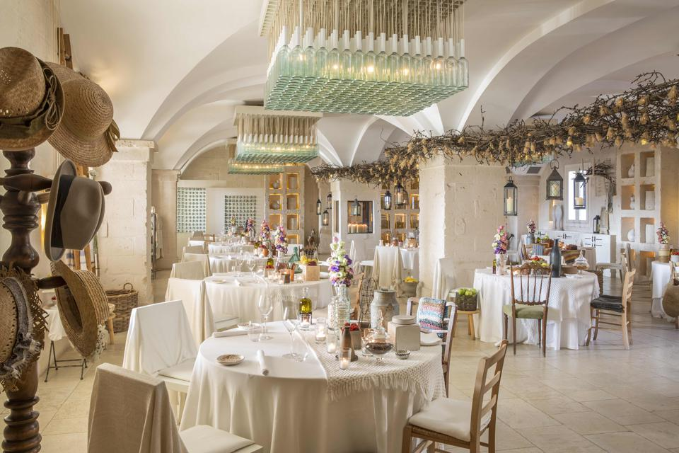 The dining room at Due Camini at Borgo Eganzia is decorated with hats and glass bottles