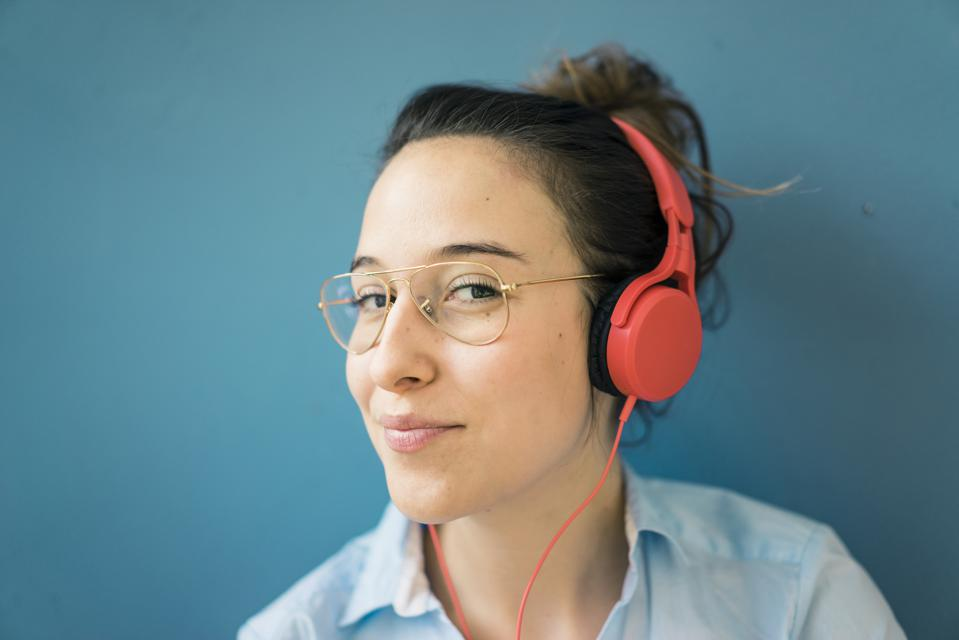 Portrait of smirking woman listening with headphones