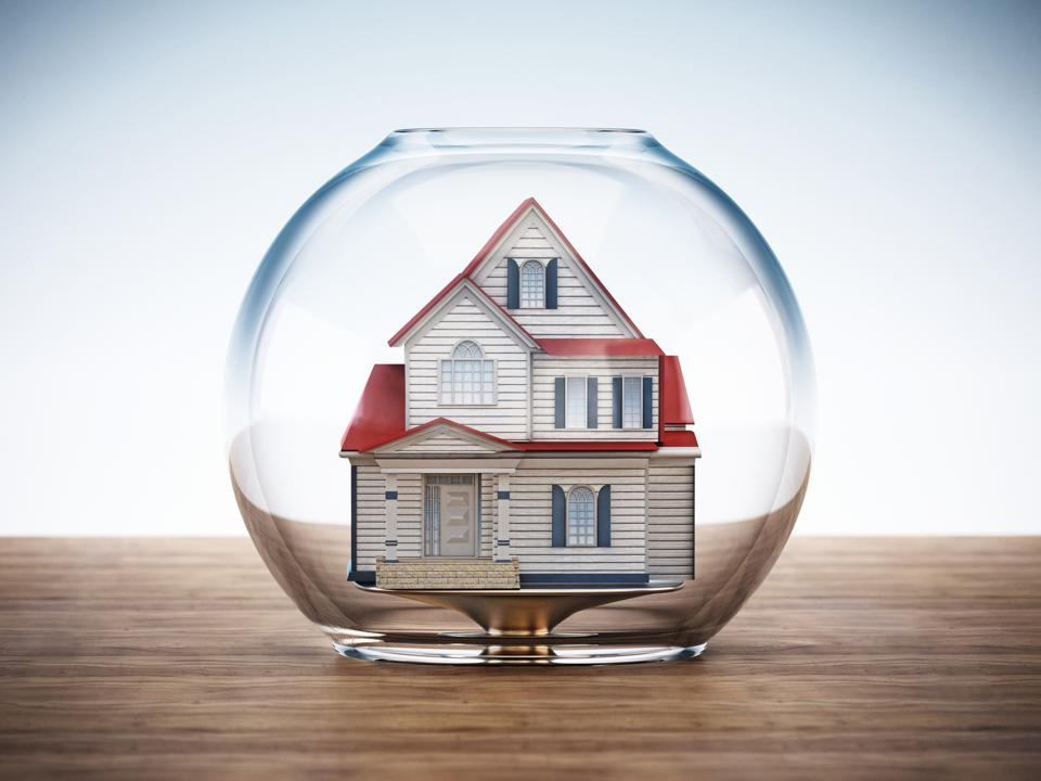 House standing inside fish bowl on wooden surface