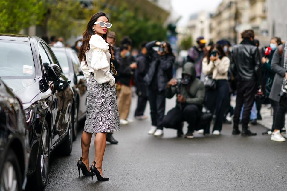 A woman posing outside a car for a street-style photograph at Paris Fashion Week Womenswear Spring Summer 2021