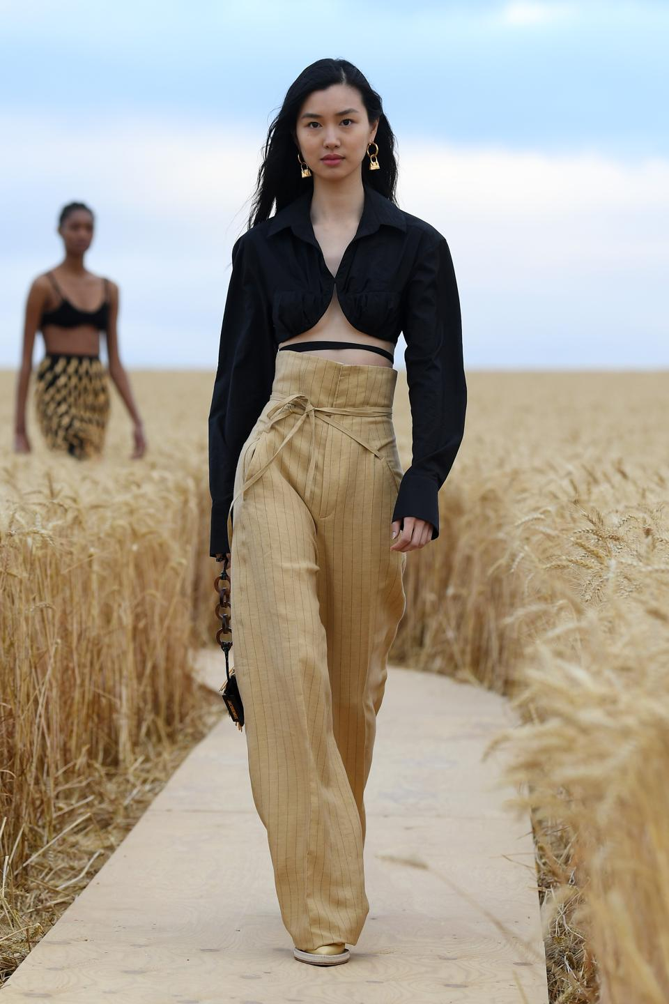 A model in a black cardigan and tan pants walks on a runway in a wheat field