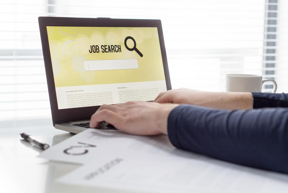 Man trying to find work with online job search engine on laptop. Jobseeker in home office. CV and application paper on table. Motivated applicant. Modern job hunting, seeking and unemployment concept.