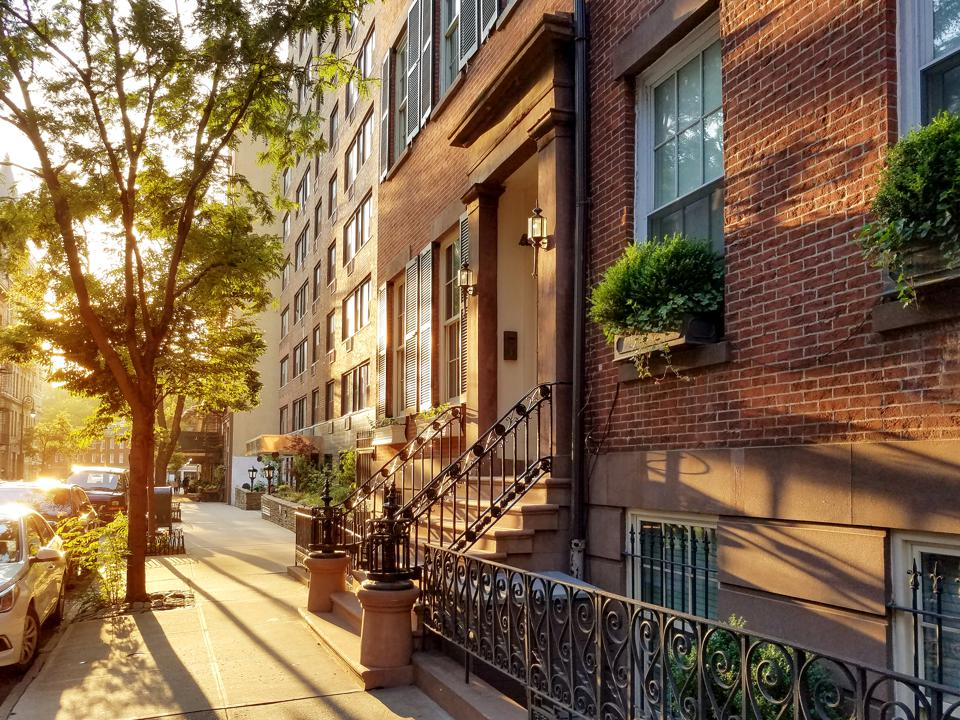 Old brownstone buildings along a quiet neighborhood street in New York City