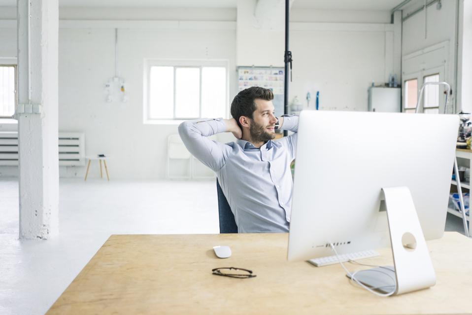 Smiling businessman sitting at desk in office having a break