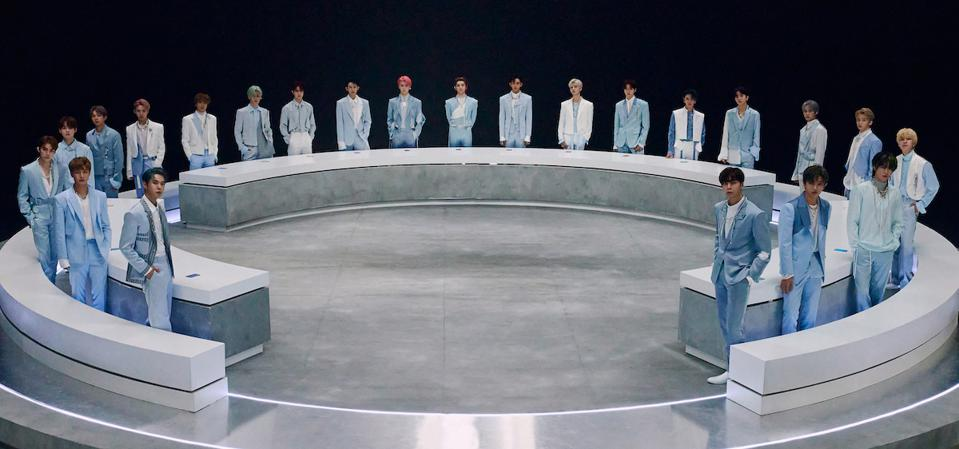 23 members of NCT 2020 standing up in a circle