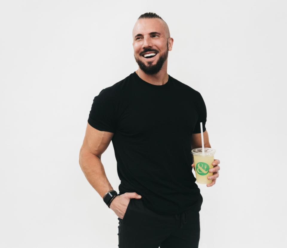 Steele Smiley smiles holding a drink and wearing all black.
