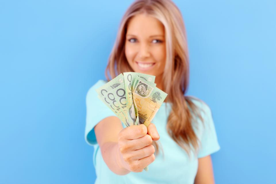 Smiling woman holding up Australian money