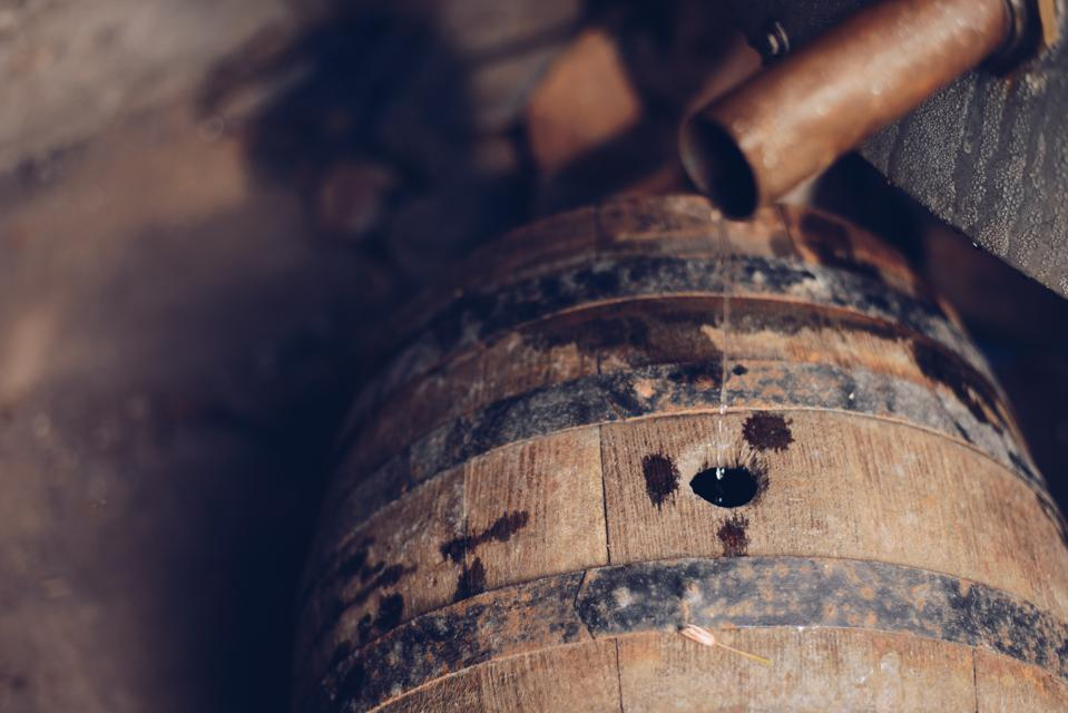 Moonshine Alcohol Flowing from the copper pipe to the old wooden barrel