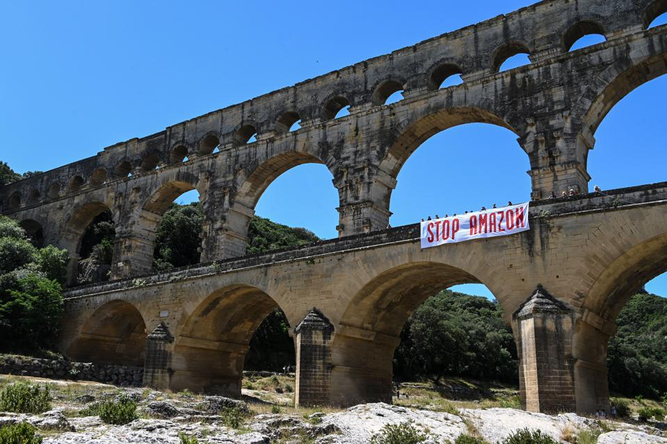 Activists stand on the Pont du Gard bridge next to a banner reading ″Stop Amazon″ in southern France.