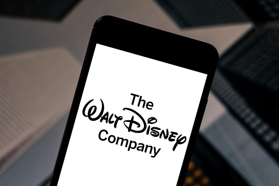 In this photo illustration The Walt Disney Company logo is...
