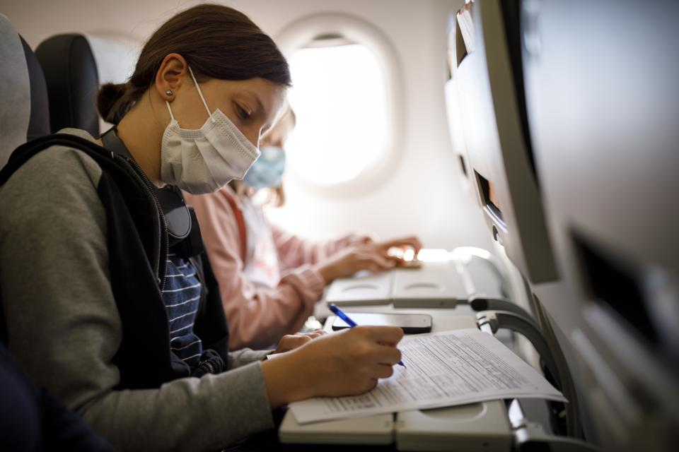 Two kids travelling during the coronavirus pandemic by an airplane, filling out paperwork