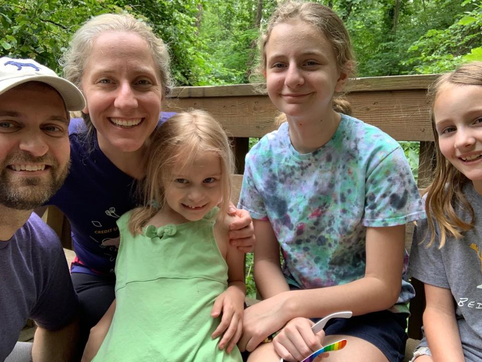 A blonde woman smiles for a photo with her husband and three young daughters.