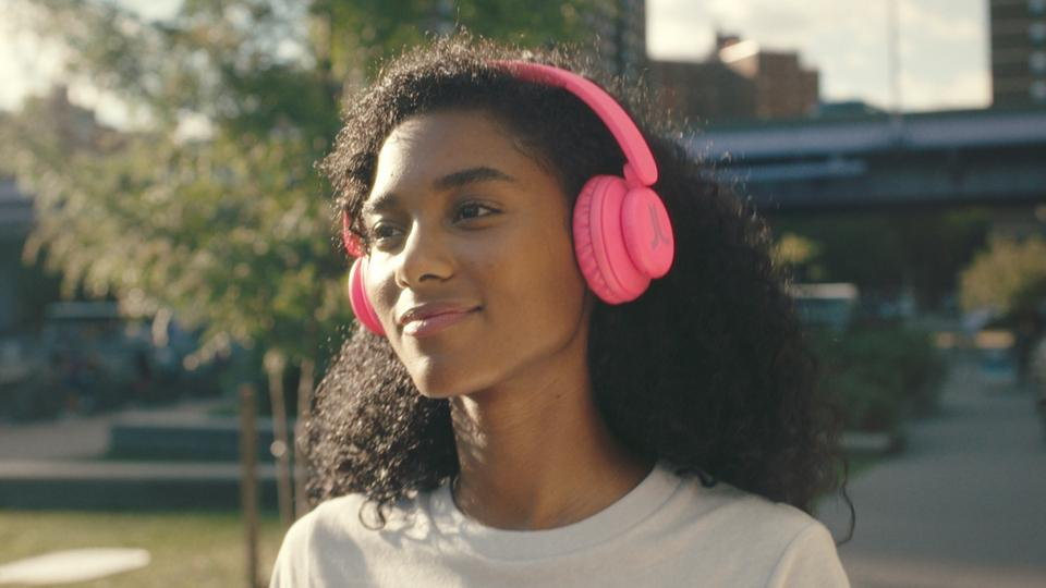 Woman wearing pink WeSC headphones