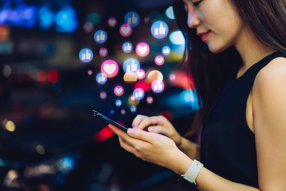 Beautiful young Asian woman using smartphone on social media network application on the go, viewing or giving likes, love, comment, friends and pages in the city at night. Social media addiction concept