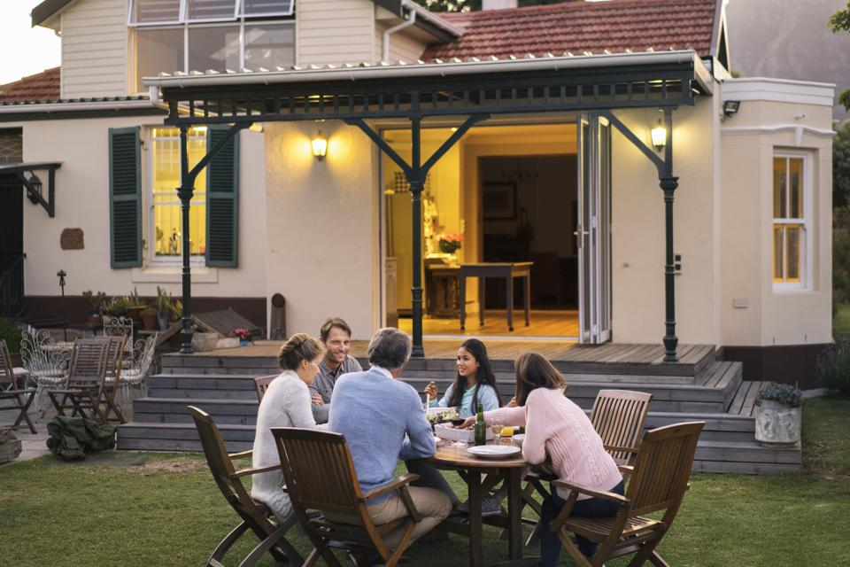 Family having food while sitting outside house