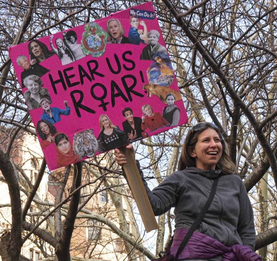 Woman holding ″hear us roar″ sign