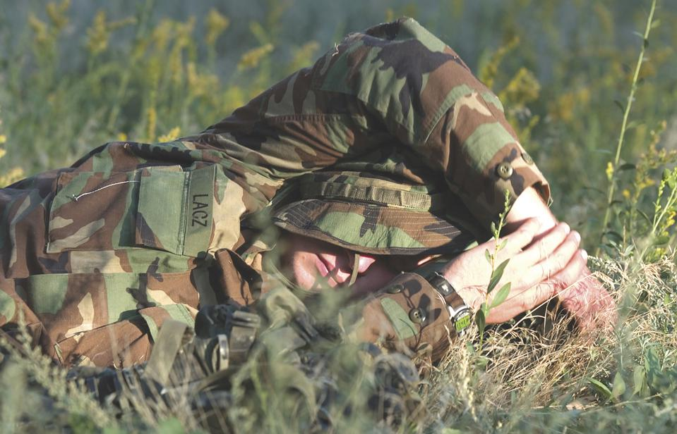 A tuckered trainee reclines on a bed of spring wildflowers in between land navigation exercises.
