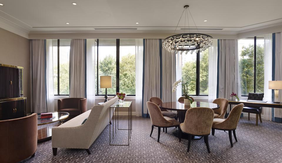 A hotel suite living room with contemporary furniture in shades of taupe and beige