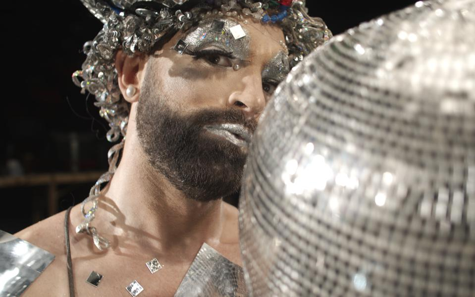 bearded man in drag with disco ball
