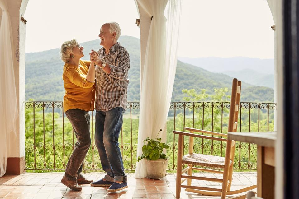 Loving senior couple dancing in balcony at home