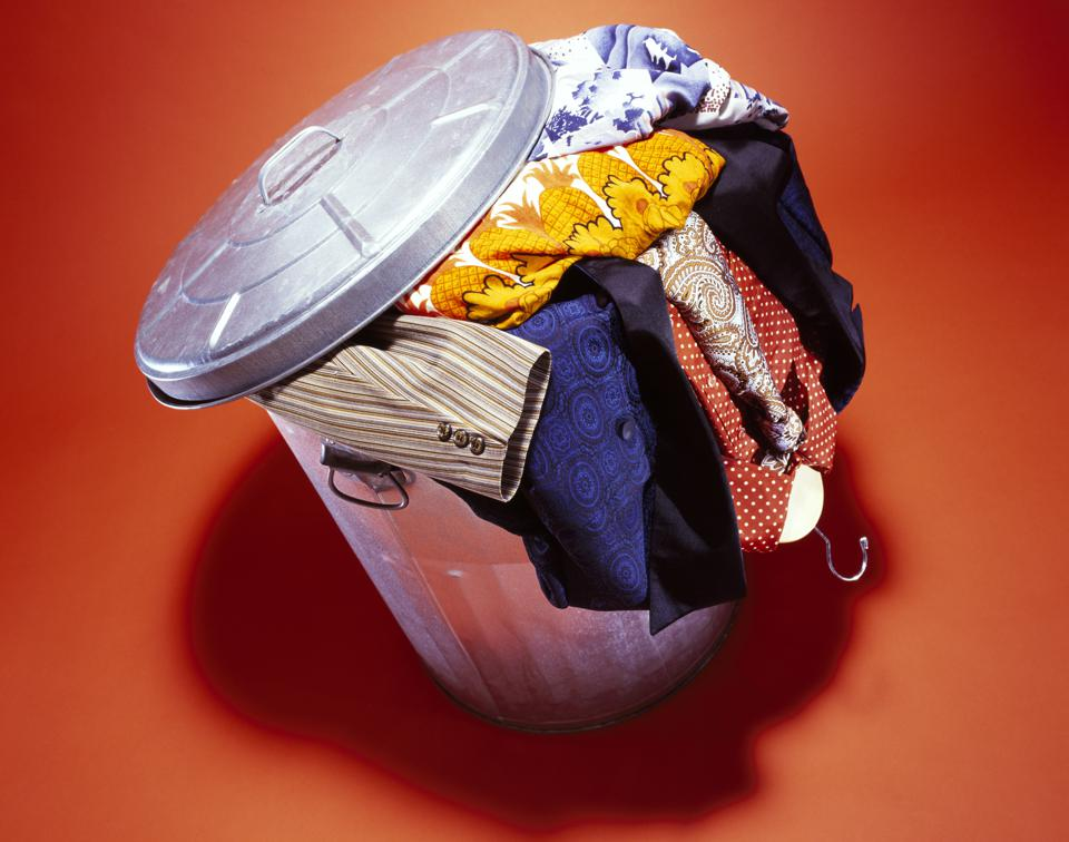 Used clothing overflowing in trash can