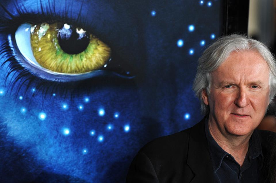 James Cameron, the director of AVATAR standing in front of his movie poster.
