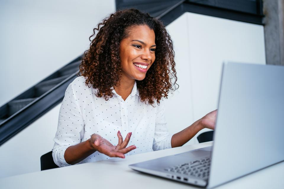 Businesswoman meets with colleagues virtually.