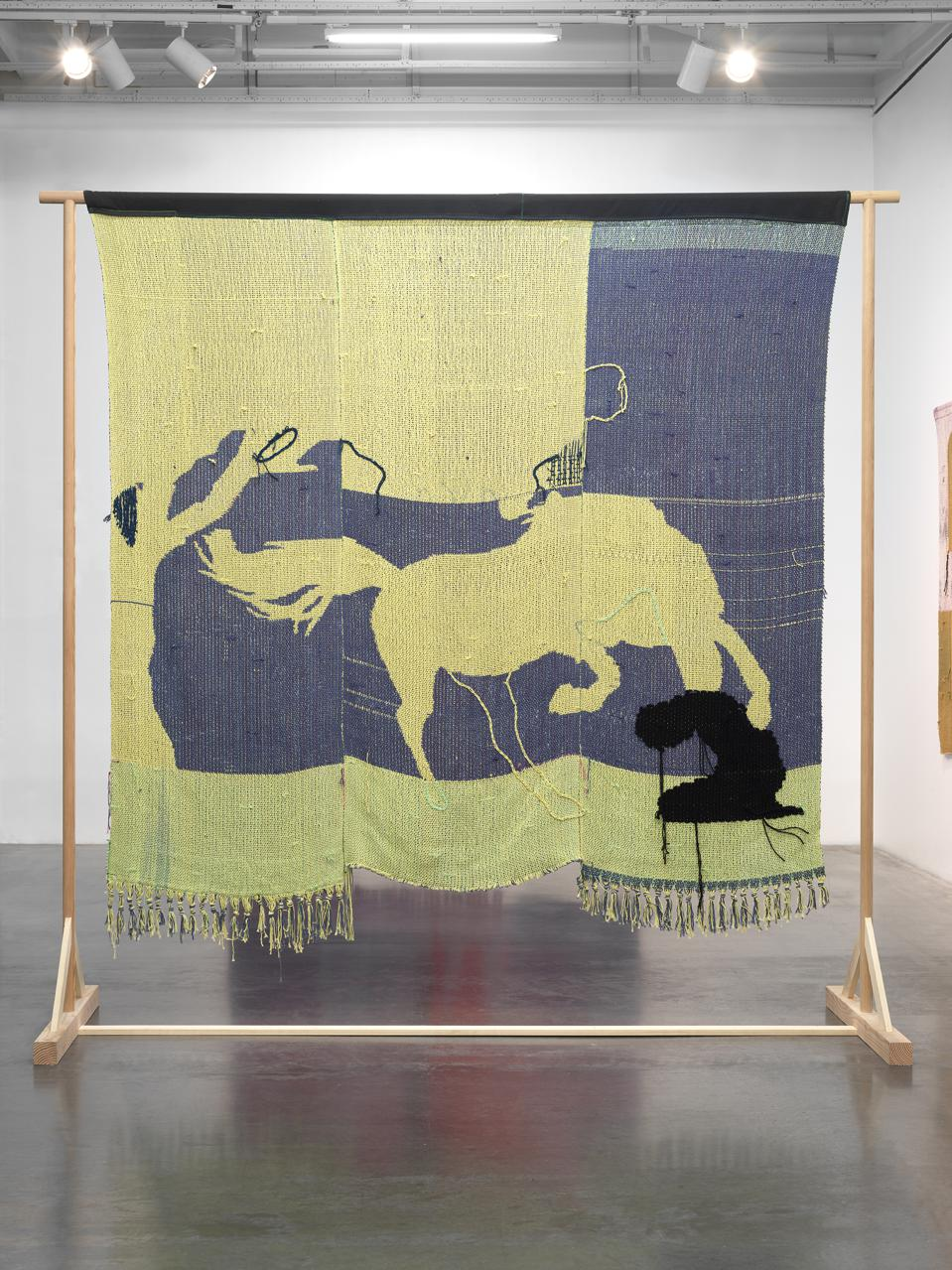 A tapestry by Diedrick Brackens that shows a man kneeling before a horse