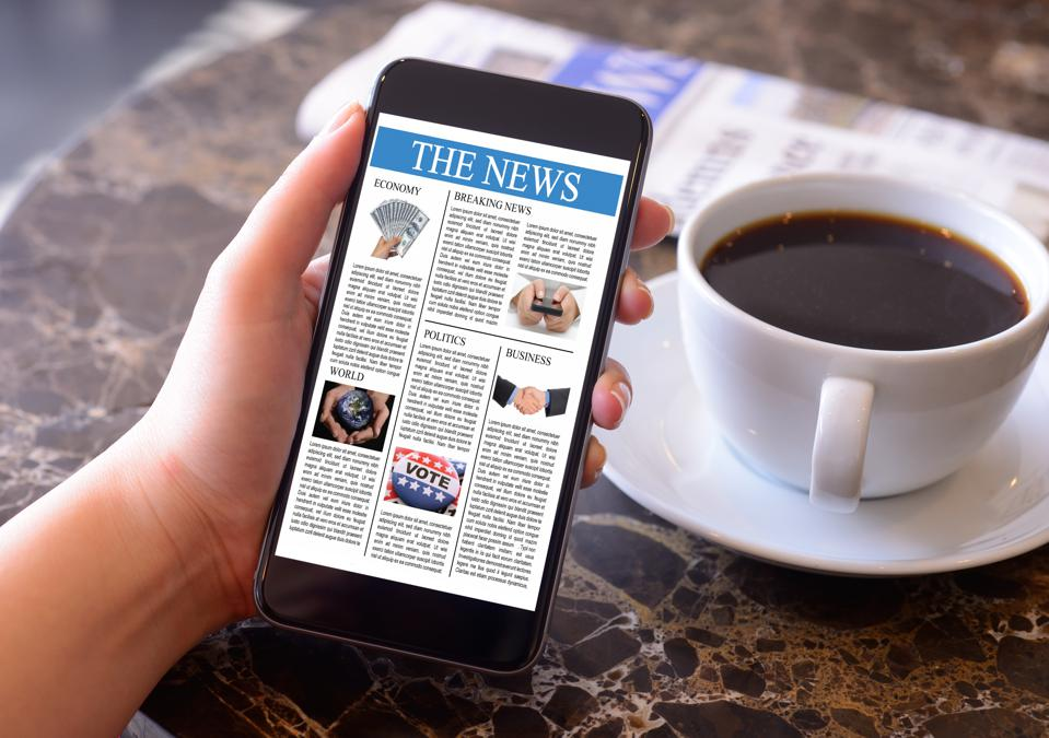 Hand holding smartphone displaying news