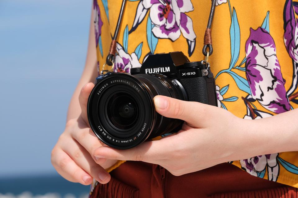 Close up of person holding a Fujifilm X-S10 with lens