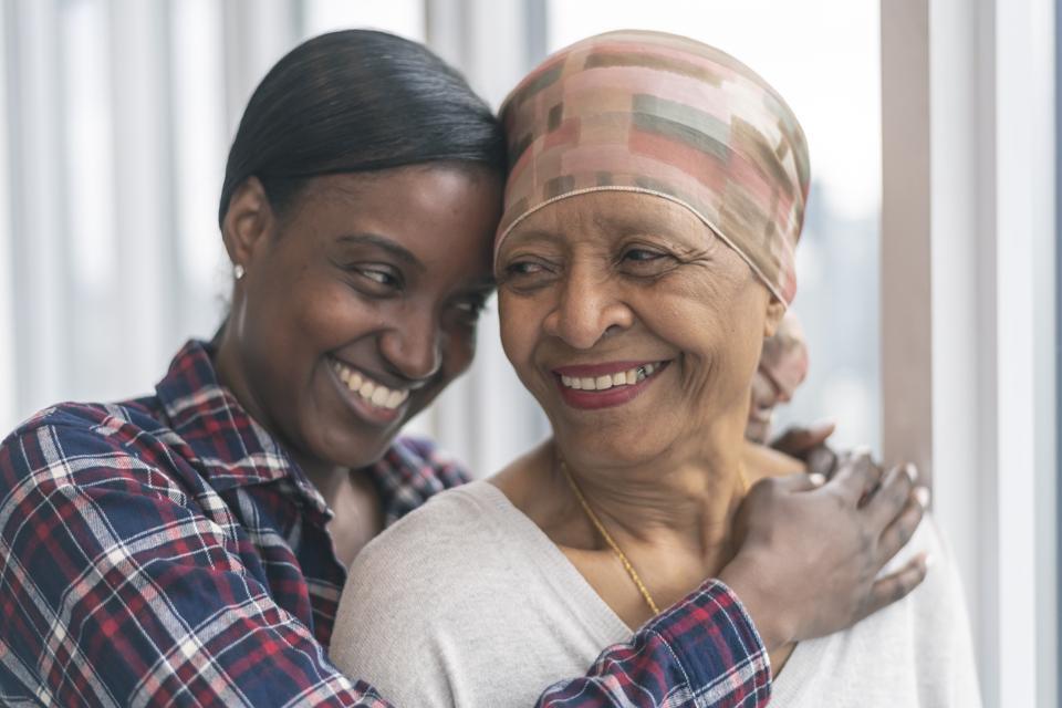 Two black women embrace.