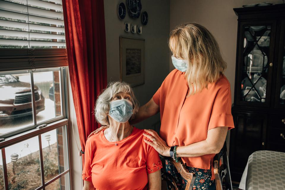 A caretaker baby boomer daughter talking with her mother in her 80s wearing protective mask