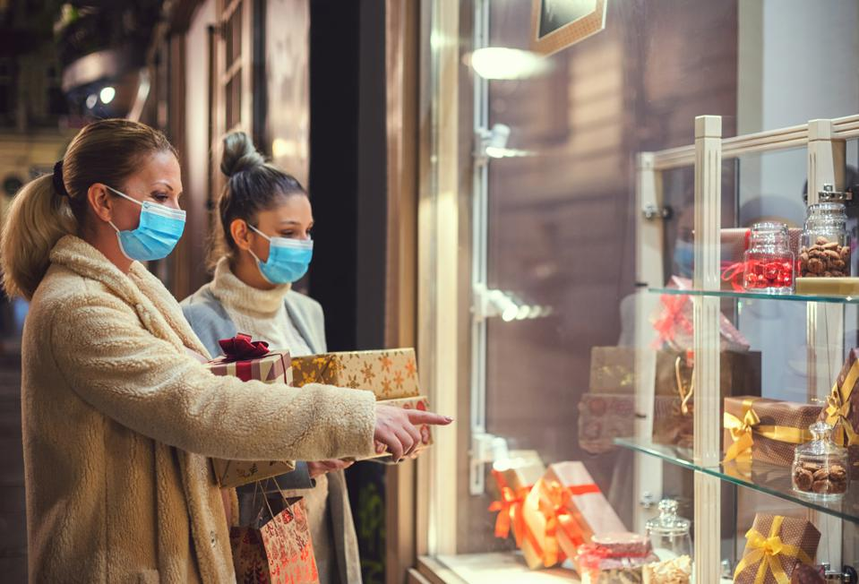 Family shopping for holiday gifts during the COVID-19 pandemic. They wear a protective mask to protect themselves from COVID-19.