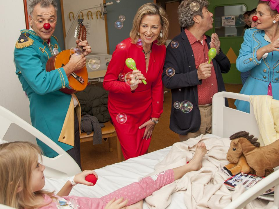 A group of doctors dressed in red clown noses entertains a sick child with bubbles.