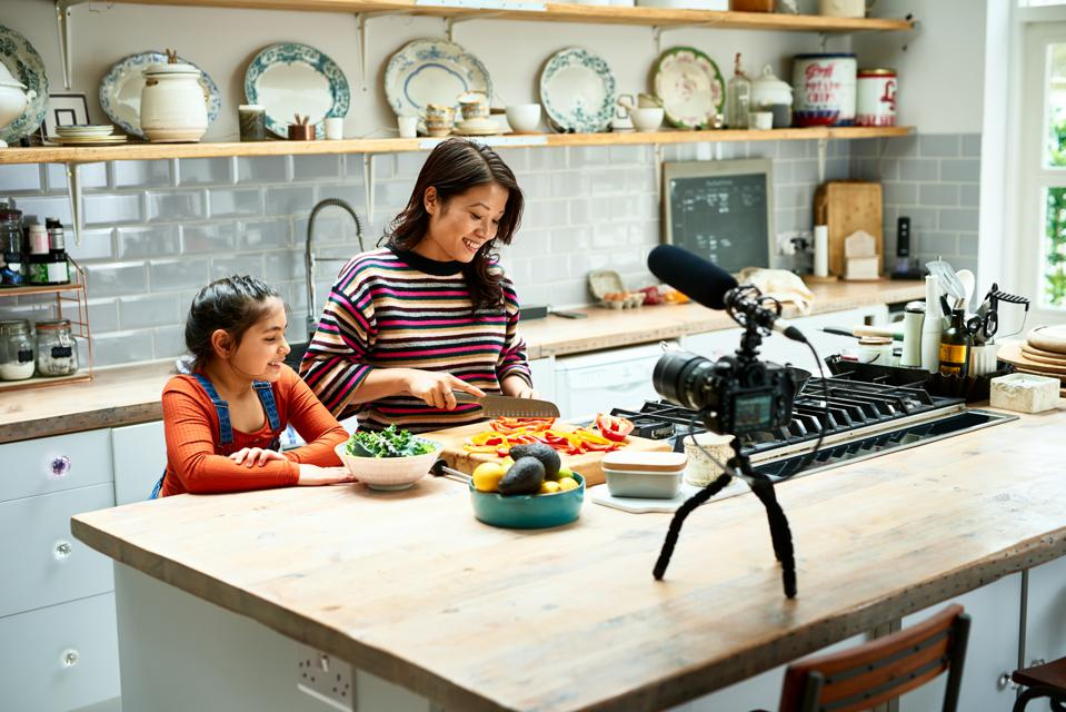 Daughter helping mother prepare healthy meal in kitchen