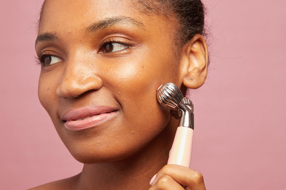 Black woman holding a cleansing beauty tool to her cheek